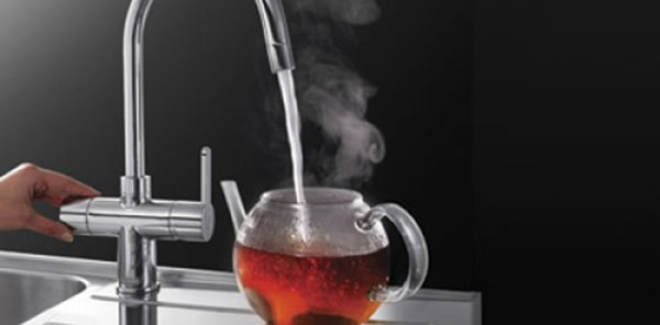 Filling a glass teapot with water from a boiling-water tap