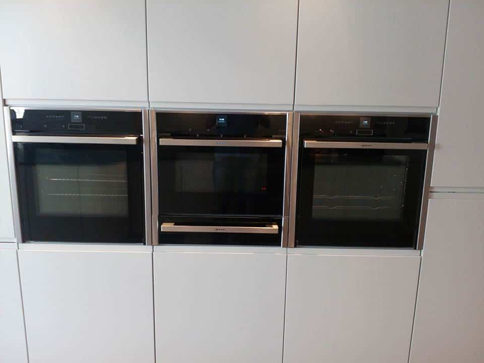 Three integrated ovens with white kitchen units